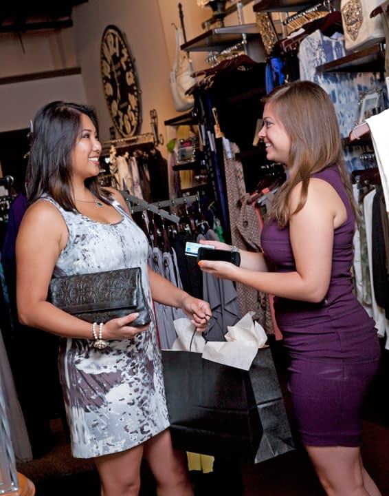 Customer with Saleswoman Making Mobile POS Sale